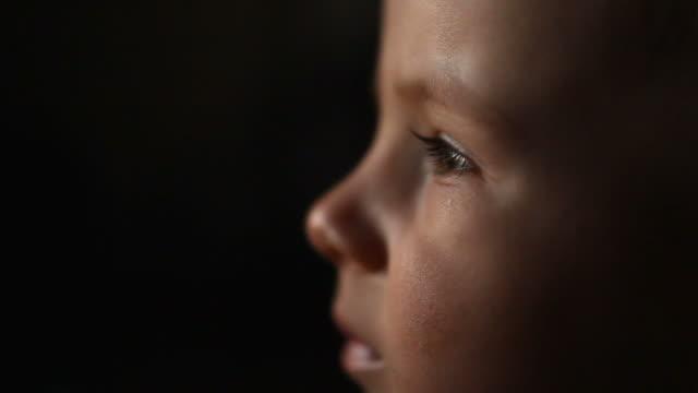 vídeos de stock e filmes b-roll de tired baby lost in front of television, wrong education, boy portrait, sad childhood, black background, blink, eyes - tv e familia e ecrã