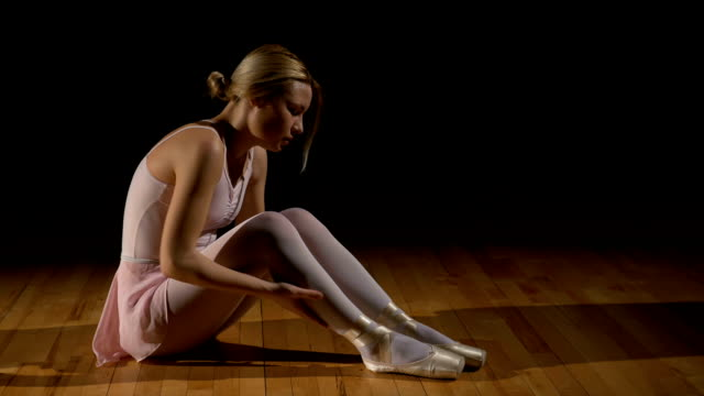 疲れたバレエダンサーは彼女の足をこすり - バレリーナ点の映像素材/bロール
