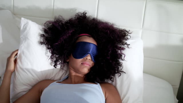 vídeos de stock e filmes b-roll de tired black girl waking up in bed with sleep mask - afro latino mask