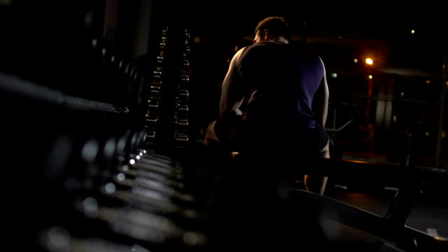 Tired bodybuilder sits on bench in gym hunched up, thinks over training program video