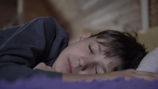 stockvideo's en b-roll-footage met vermoeide jongen liggend op het bed en kijken uit het raam, de jongen net wakker - sleeping illustration