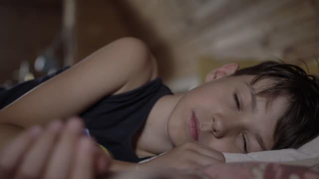 피곤한 소년은 침대에 누워찾고, 소년은 그냥 일어났다 - 소년 스톡 비디오 및 b-롤 화면