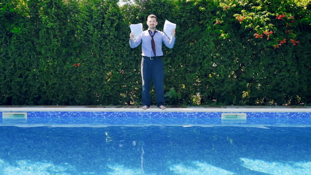 Tired businessman throws documents and jumps in swimming pool in suit video