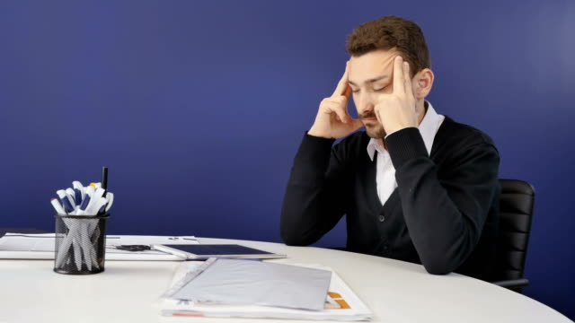 Tired businessman with headache in the office video