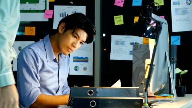 疲れたビジネスマンは、オフィスで働きます。多くのやるべきことと彼を持つビジネス仕事一日すべての夜。 - ビジネスマン点の映像素材/bロール