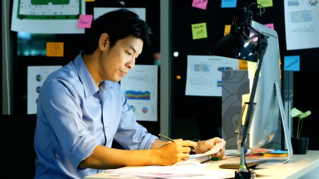 疲れたビジネスマンは、オフィスで働きます。彼は夜遅く以来取り組んでいます。 - 悩む点の映像素材/bロール