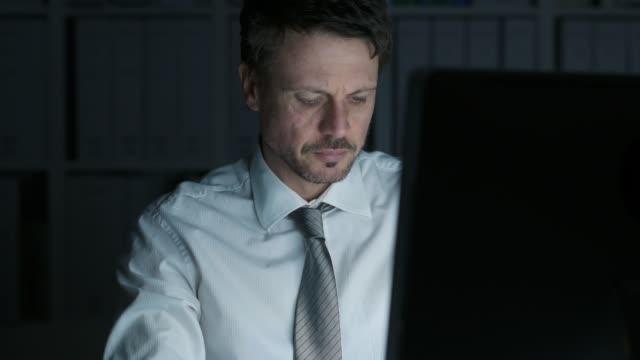 Homme d'affaires fatigué travaillant tard dans la nuit au bureau et avoir une douleur au cou, il est en contact avec son cou - Vidéo