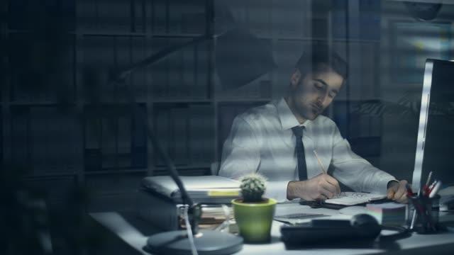 tired businessman working late at night - работа допоздна стоковые видео и кадры b-roll