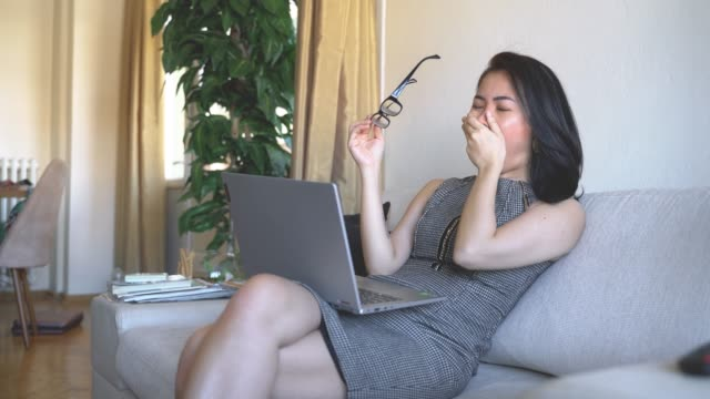 Tired businesswoman yawning at home office
