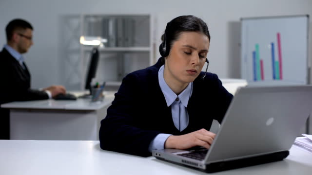 Tired call center operator taking off headset and closing laptop, workday end