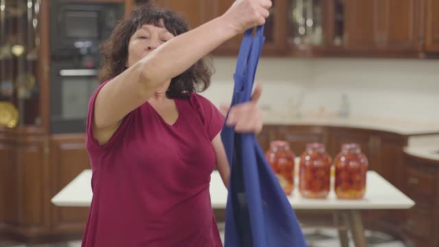 vídeos de stock e filmes b-roll de tired caucasian retiree taking off blue apron and fixing her curly hair. senior woman standing at the kitchen with bottles of tomatoes at the background. hobby, household. - avental