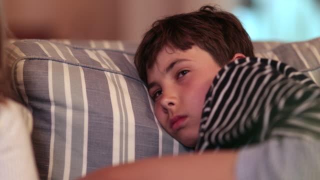 vídeos de stock e filmes b-roll de tired child boy falling asleep on sofa while watching tv screen. bored exhausted kid - tv e familia e ecrã