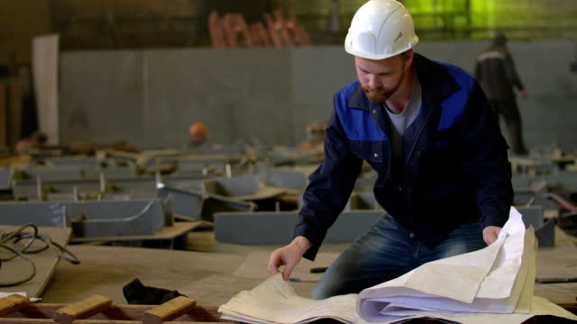 Tired Construction Engineer Look At Building Plans In Heavy
