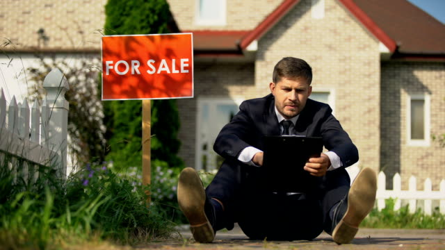 Tired estate broker sitting on ground near for sale signboard, failed contract