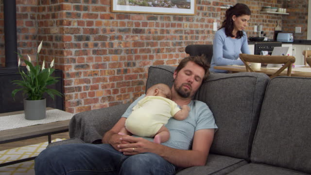 Tired Father With Baby Son Sleeping On Sofa Together video