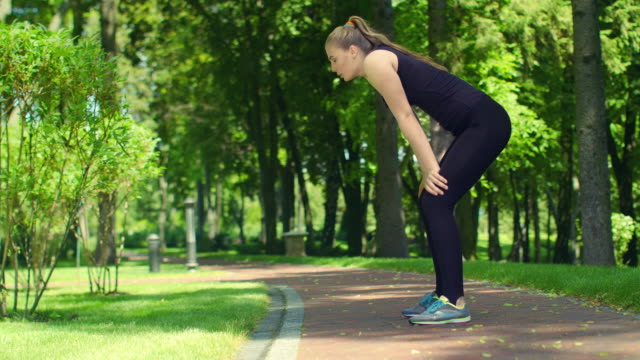 Tired female athlete after running hard outdoor. Fitness woman relaxing video