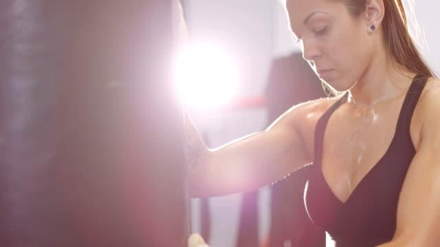 vídeos de stock, filmes e b-roll de cansado boxer fêmea descansando com os braços sobre o saco de pancadas - autodefesa