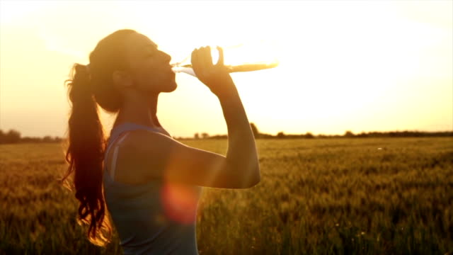 Tired Female Jogger Drinking Water Beautiful Summer Sunset video