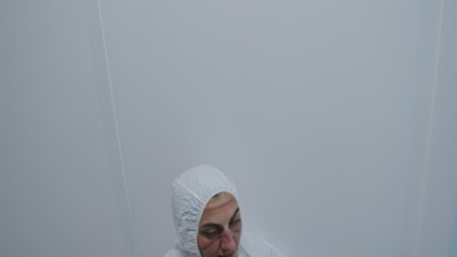 trött kvinnlig medicinsk arbetare med ansiktsärr från skyddande uniform efter överarbete med patienter coronavirus infekterade tar av skyddande mask och vila i korridoren av modern klinik - face mask bildbanksvideor och videomaterial från bakom kulisserna