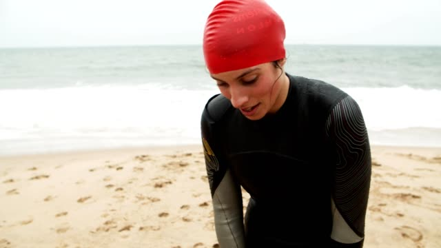 tired female swimmer on beach - sportsmenka filmów i materiałów b-roll
