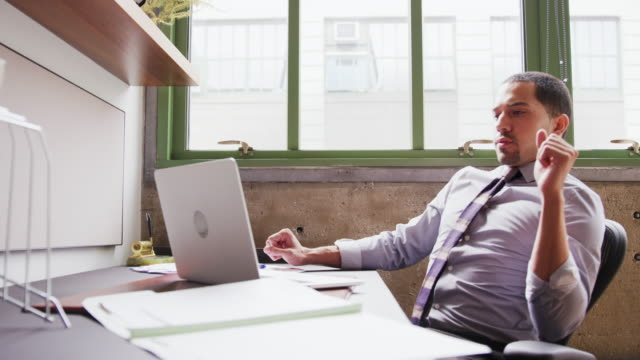 Tired Hispanic businessman working with laptop in office Tired Hispanic businessman working with laptop in office leaning stock videos & royalty-free footage
