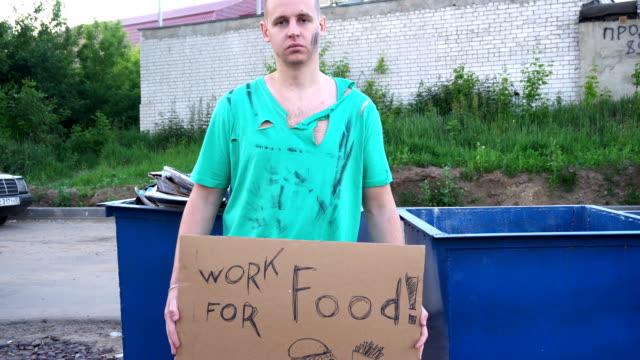 trött hobo mannen på gatan. anmäl på kartong - kommer att arbeta för mat - dirty money bildbanksvideor och videomaterial från bakom kulisserna