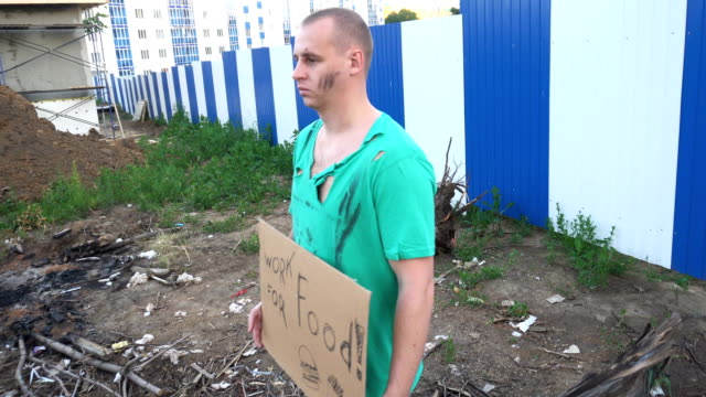 Tired hobo man on the street. Sign on cardboard - will work for food video