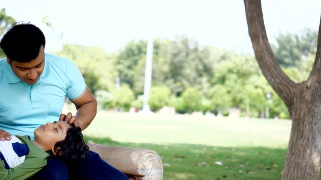 bir bahçenin bankında otururken babasının kucağında uyuyan yorgun hintli çocuk - yaşam tarzı aileleri - orta plan plan türleri stok videoları ve detay görüntü çekimi