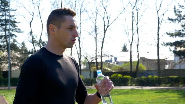 trött jogger i sportkläder dricksvatten från plastflaska efter marathon i park - tävlingsdistans bildbanksvideor och videomaterial från bakom kulisserna