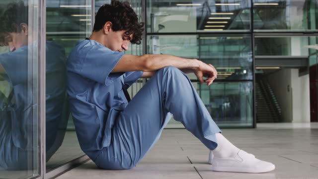 Tired junior doctor wearing scrubs sitting against wall in modern hospital building - shot in slow motion Tired Young Male Doctor Wearing Scrubs Sitting Against Wall In Modern Hospital Building exhaustion stock videos & royalty-free footage