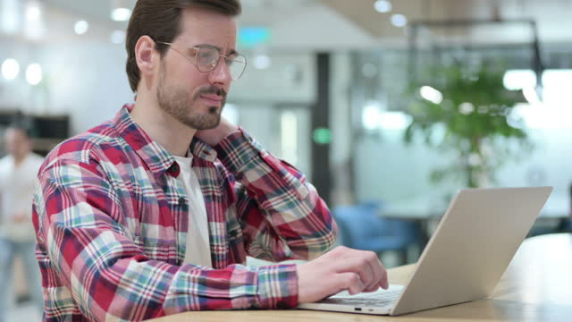 Tired Male Designer with Laptop having Neck Pain