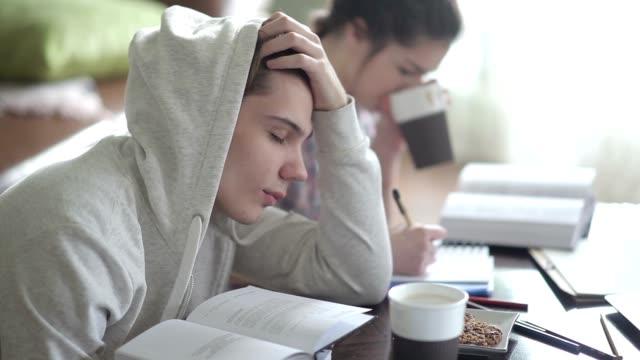 vídeos de stock e filmes b-roll de cansado homem aluno com camisolas com capuz quedas adormecer. - cansado