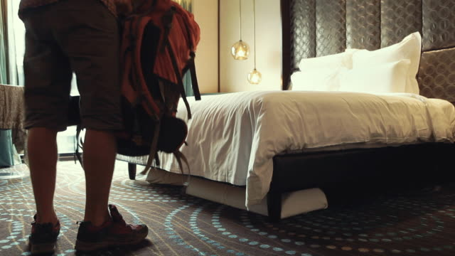 tired male traveller coming to hotel room putting down his backpack and sitting on bed. travel concept. - турист с рюкзаком стоковые видео и кадры b-roll