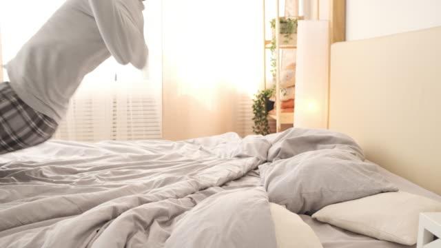 uomo stanco che si addormenta su un letto accogliente - sonnecchiare video stock e b–roll