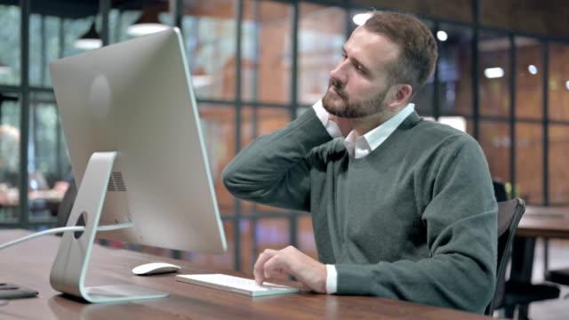 vídeos de stock, filmes e b-roll de homem tired que tem a dor de garganta ao trabalhar no computador - ortopedia