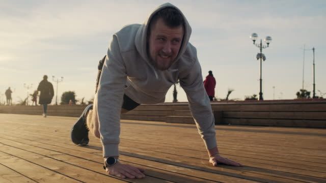 Tired man is doing physical exercises in park area of city in sunset time - vídeo