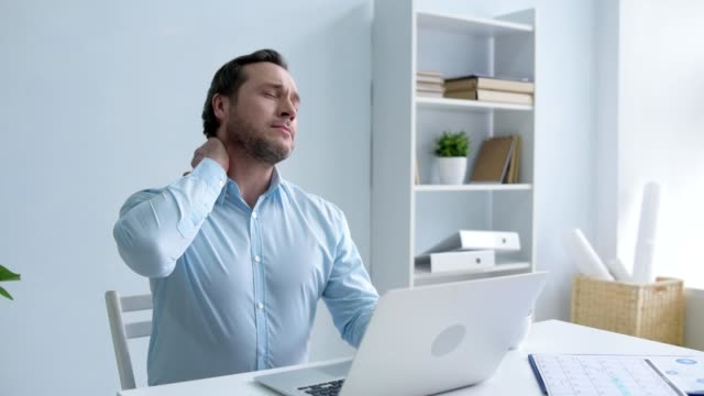 Tired man massaging neck while working on laptop video