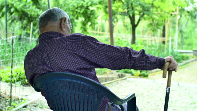 tired man sitting alone with hand leaned on a walking stick: elderly, senior footage of a retired old man sleeping on a chair outdoor in countryside leaning stock videos & royalty-free footage