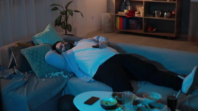 vídeos de stock e filmes b-roll de tired man sleeping on sofa - sofá