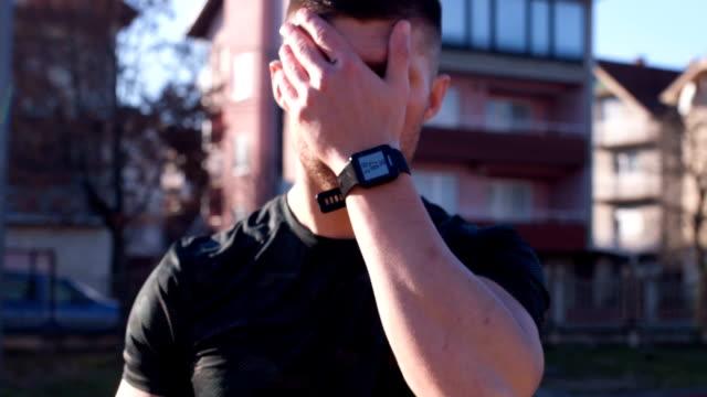 trött man torkar svetten ur ansiktet efter träningspass - svett bildbanksvideor och videomaterial från bakom kulisserna