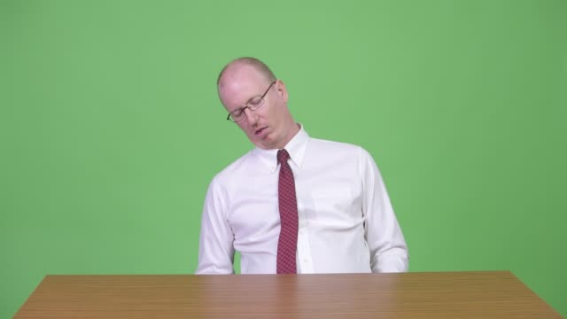 Tired mature bald businessman falling asleep at work and looking guilty Studio shot of mature bald businessman sitting behind desk against chroma key with green background man sleeping stock videos & royalty-free footage