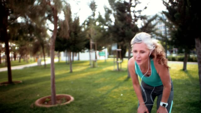 Tired mature woman relaxing after jogging in the park