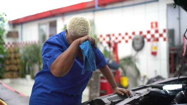 vidéos et rushes de femme fatigué de mécanique avec le mal de tête dans le travail de réparation d'automobile - 40 44 ans