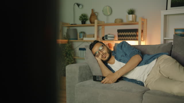 tired middle eastern man sleeping on couch in front of tv lying alone - sonnecchiare video stock e b–roll