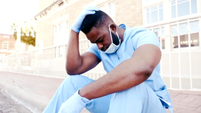 Tired nurse taking a break from COVID-19 unit An upset mid adult African American male registered nurse sits on a curb outside the hospital building. As he reflects on what he has seen in the COVID-19 unit, he places his head in his hands. black people stock videos & royalty-free footage