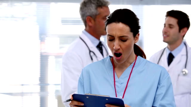 Tired nurse with clipboard video