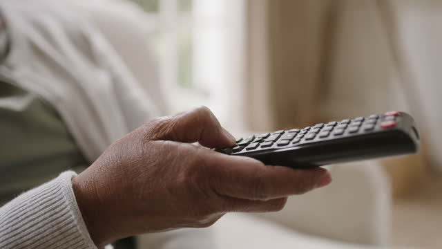 Tired of watching the same shows? 4k video footage of a senior woman using a remote control while sitting at home changing channels stock videos & royalty-free footage