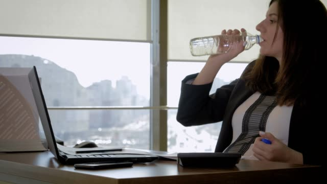 Tired Of Working Pregnant Woman Businessman In Office Drinking Water From Bottle