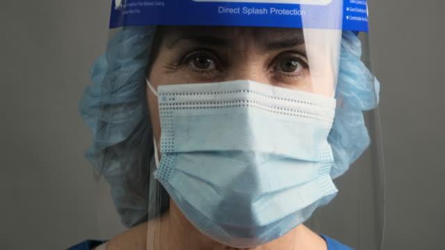 trött, överarbetad, utmattad sjukvårdspersonal bär en mask och en ansiktssköld poserar tittar på kameran - hospital studio bildbanksvideor och videomaterial från bakom kulisserna