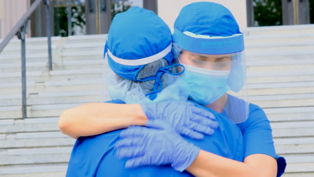 Tired, overworked, exhausted health care workers embracing outside the hospital while taking a break Tired, overworked, exhausted health care workers embracing outside the hospital while taking a break nurse stock videos & royalty-free footage